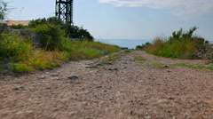 The camera at a low height over the path. On the horizon you can see the sea. Stock Footage