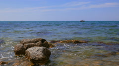 Stones in the waves of the sea against the backdrop of the horizon. - stock footage