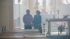 Older couple holding hands walking up to the pew - stock footage