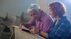 Two older Christians reading the Bible in the church pew Stock Footage