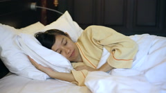 Video Asian woman sleeping tight in bed Stock Footage