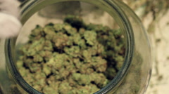 Hand in jar of Medical marijuana showing product - stock footage