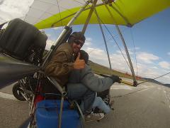 Hang Gliding take off tandem flying above fields and forests. - stock footage