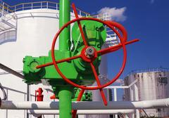green valve on a gasoline storage tank background - stock photo