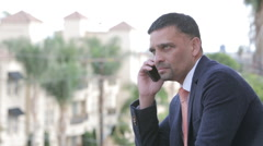 Handsome businessman talking on the phone outdoors Stock Footage