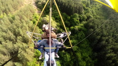 Hang Gliding tandem flying above fields and forests. Stock Footage