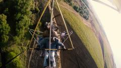 Hang Gliding tandem flying above fields and forests. - stock footage
