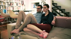 Couple sitting on the sofa and watching something on television - stock footage