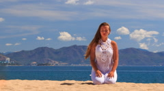 Blonde girl in lace maditates in yoga asana sits on knees Stock Footage