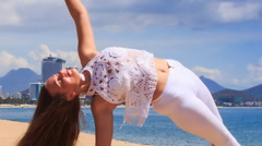 Stock Video Footage of blonde girl in lace shows yoga asana half moon on beach