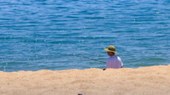 fisherman in hat fishes with rod on sand beach against azure sea - stock footage