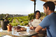 Happy young couple at winery restaurant - stock photo