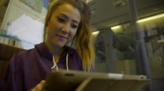 Smiling girl uses tablet computer on subway Stock Footage