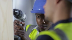 4k Male construction worker or tradesman working with female apprentice Stock Footage