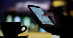 Drinking coffee tea using smartphone stock market Stock Footage