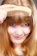 Closeup woman combing her fringe with comb Stock Photos