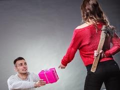 Trusting guy giving present to misleading girl Stock Photos