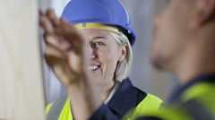 4k Male construction worker or tradesman working with female apprentice - stock footage