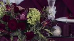 flowers and candles as a decoration of a festive table at a restaurant - stock footage