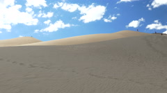 4K sun comes out from clouds on great sand dune Stock Footage
