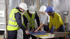 4k Confident female engineers looking at blueprints with male colleagues - stock footage