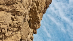 Vertical shot of Close up time lapse of rock pile, clouds moving across sky Stock Footage
