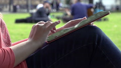 Woman with tablet on her knees sitted near a tree in a city park Stock Footage