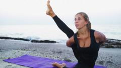 Young female practices yoga on the beach slow motion Stock Footage