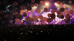 Many balloons falls on people in the concert hall Stock Footage