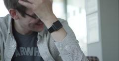 Man laughing and wearing a smart watch in a hotel lobby Stock Footage