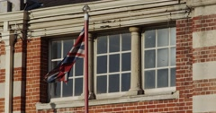 Slow Motion Union Jack Flag in front of Heritage British Building Stock Footage