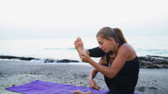 young female practices yoga on the beach slow motion - stock footage