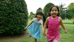 Asian sisters running around in the park and laughing together, Slow motion shot Stock Footage