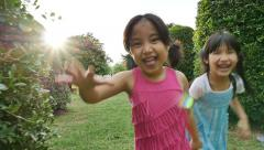 Asian sisters running around in the park and laughing together, Slow motion shot - stock footage