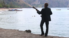 Guitarist plays against beach with longtail boats Stock Footage