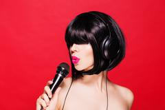 Stock Photo of Stylish girl singing with a microphone, red background. Karaoke