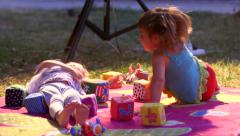 Little kids girls playing joyfully in the park on bedding with a box of bricks - stock footage