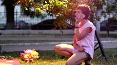 Short hair woman on the phone while a child play toys in park Stock Footage