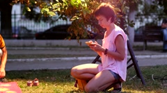 Short hair woman slide and type phone touch screen while a child play toys Stock Footage