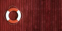 Stock Photo of Red and white life buoy hanging on the side of a wooden ship