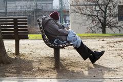 Homeless man sleeping on a bench in a one-way street Stock Photos