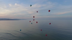 Chinese lanterns flying in the air over the ocean and mountains Stock Footage