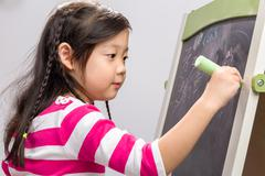 Young girl writing on blackboard on white background. - stock photo