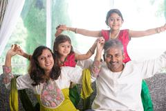 Happy Indian family playing at home - stock photo