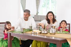 Indian family dining in kitchen - stock photo