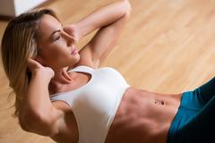 Beautiful young woman in sports clothing training her abs - stock photo