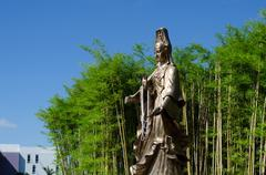 Guan Yin, Goddess of Mercy, with Bamboo Garden in background - stock photo