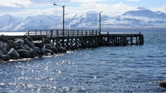 Majestic pier in dreamy blue fjord with snowy mountain in background Stock Footage