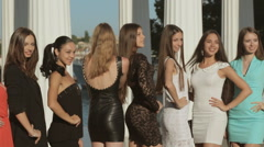 Group of girls clothed in the dresses posing near the columns Stock Footage