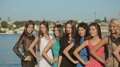 Beautiful young women clothed in a dresses posing on the background of a warship Stock Footage